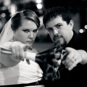 Bride and groom pointing at the camera in black and white