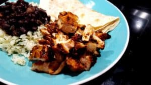 chopped chicken over rice with beans and a tortilla on a light blue plate