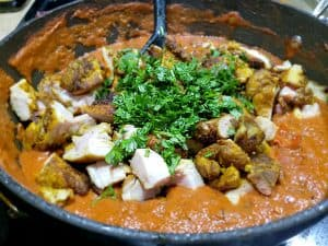 Chicken Tikka Masala Over White Rice with Cilantro Cooking in a Black Saucepot