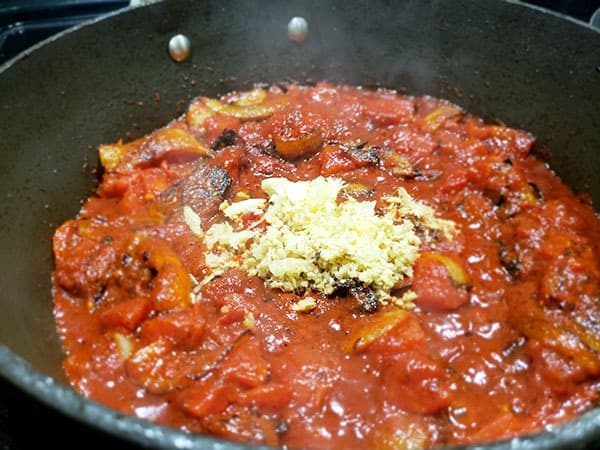 tomato suace with chopped ginger and garlic cooking with onions in a black saute pan.