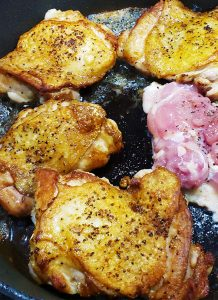 Chicken thighs cooking in cast iron pan