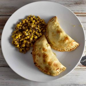 Chicken and broccoli empanada with mexican street corn on a white plate