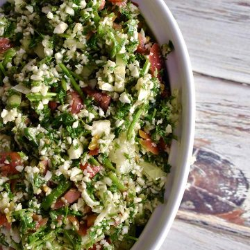 Tabbouleh in a white bowl on a white wooden table