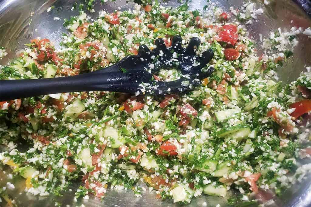 chopped salad in a metal mixing bowl with a black slotted spoon.