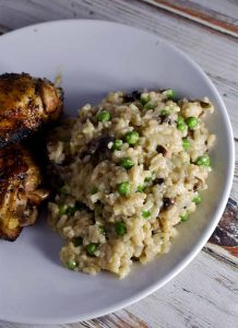 Instant Pot Risotto white mushrooms and green peas on a white plate