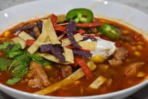 Instant Pot Chicken Tortilla Soup with jalapeno sour cream and tortilla strips in a white bowl
