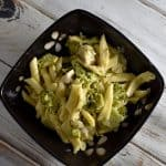 penne pasta with broccoli in a black bowl on a white wooden table