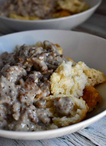 Biscuits and Gravy in a white bowl on a white wooden table