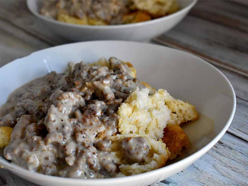 biscuits and gravy in a white bowl on a white table