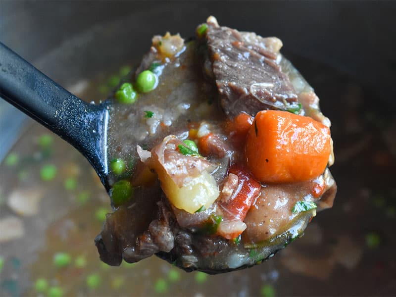 beef stew in black ladle above pot