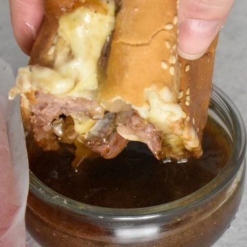 Prime Rib French Dip Sandwich dipped in au jus sauce over a white table