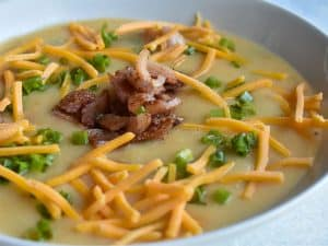 instant pot loaded baked potato soup with cheese and bacon in a white bowl