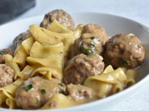 instant pot swedish meatballs in a white bowl with egg noodles