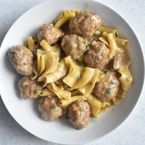 overhead shot of swedish meatballs in a white bowl on a white table