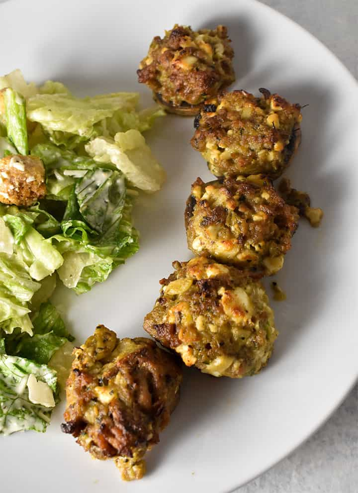 Sausage Stuffed Mushrooms on a white plate with ceasar salad