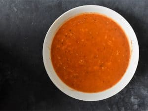 instant pot red pepper soup offcentered in a white bowl on a gray tabletop