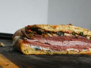muffaletta sandwich on a ciabatta bun resting on a wooden cutting board