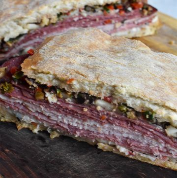 muffaletta sandwich on a wooden cutting board