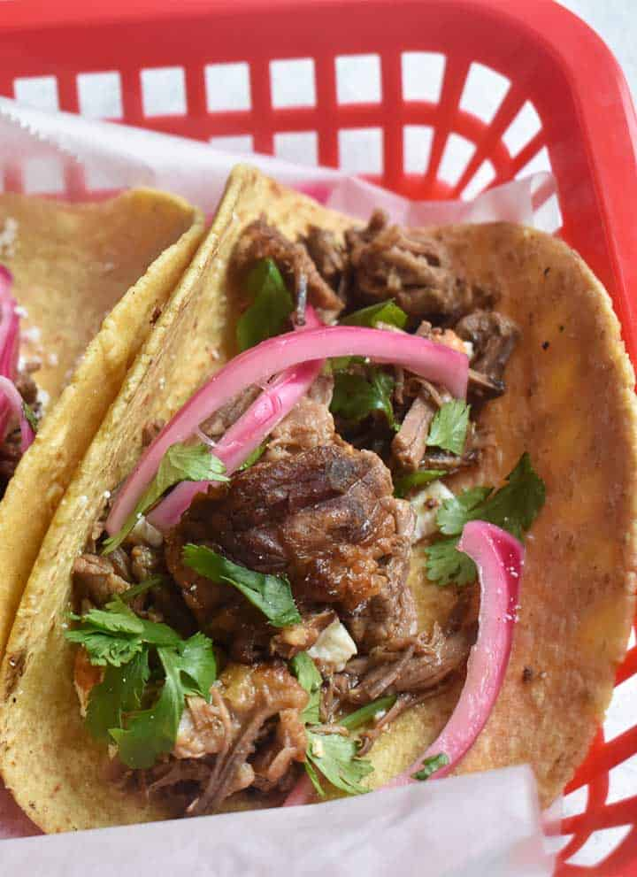 instant pot barbacoa tacos in a corn tortilla with pickled onions and cilantro in a red basket