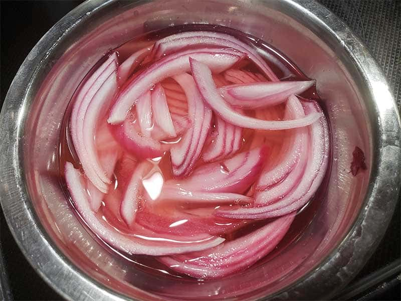 pickled red onions in a metal bowl