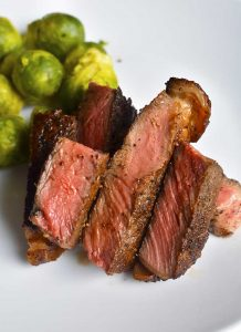 sous vide steak cooked medium rare on a white plate