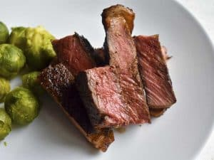 sous vide steak on white plate with brussels sprouts