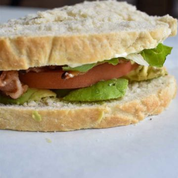 BLT Sandwich made with sous vide bacon on white bread with avocado on a white table