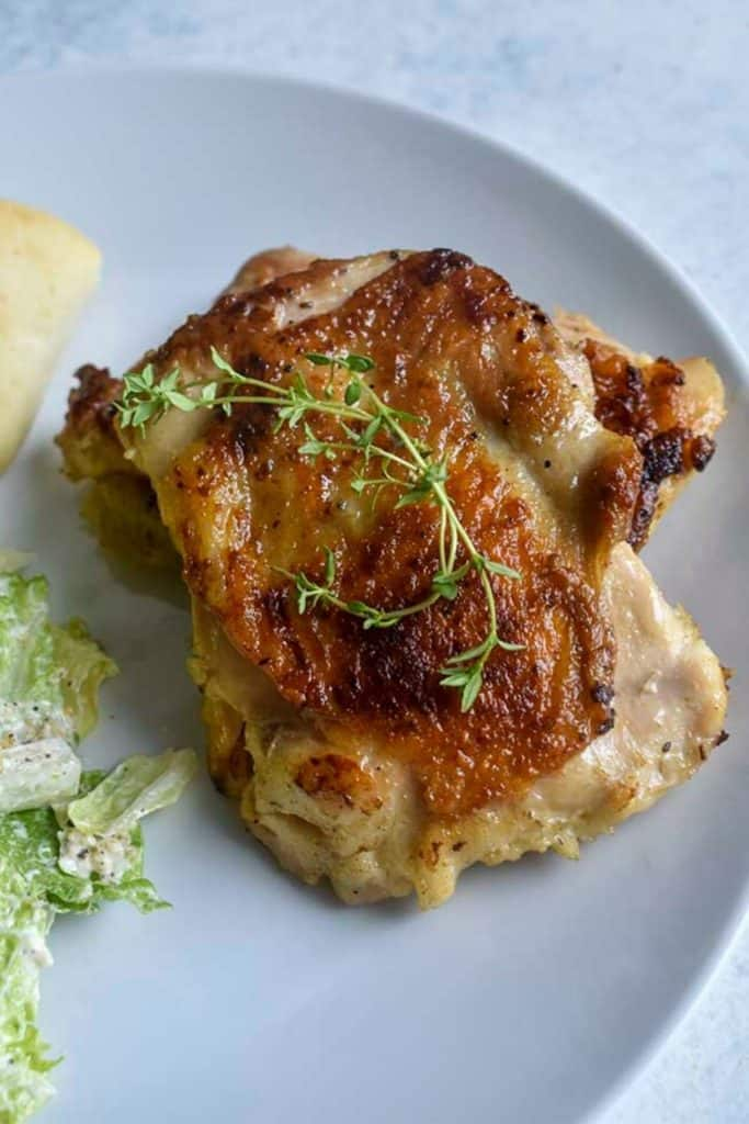 sous vide chicken thighs on a white plate - for pinterest