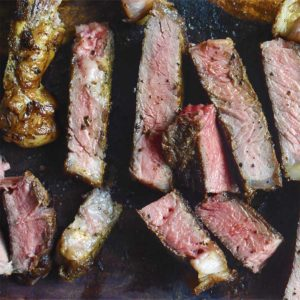 steak sliced on a wooden cutting board cooked medium rare