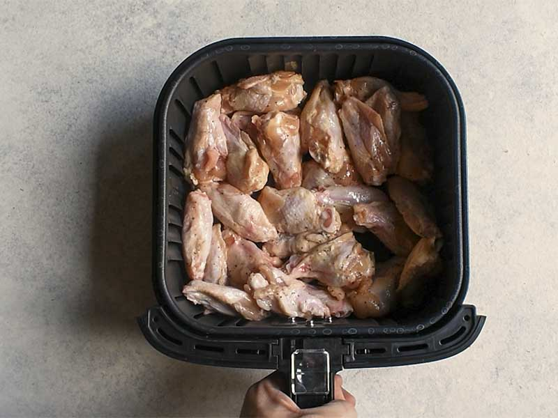uncooked chicken wings in a black air fryer basket on a white table