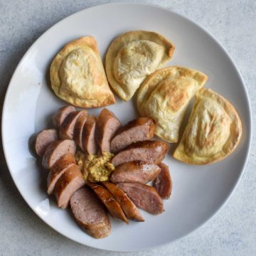 sliced sausage with pirogi on a white plate