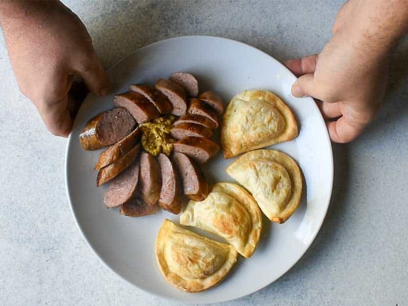 sliced sausage with dijon mustard and pirogi on a white plate being held by a hand on either side of the plate