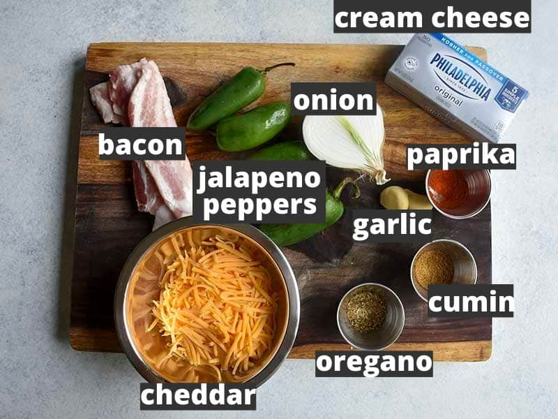 ingredients for bacon wrapped smoked jalapeno poppers on a brown wooden cutting board sitting on a white table