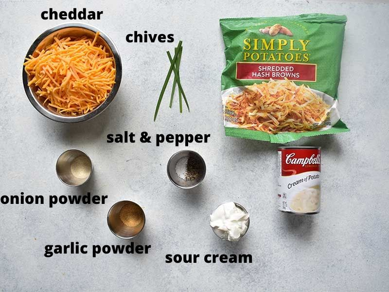 ingredients for cheesy potatoes sitting on a white table