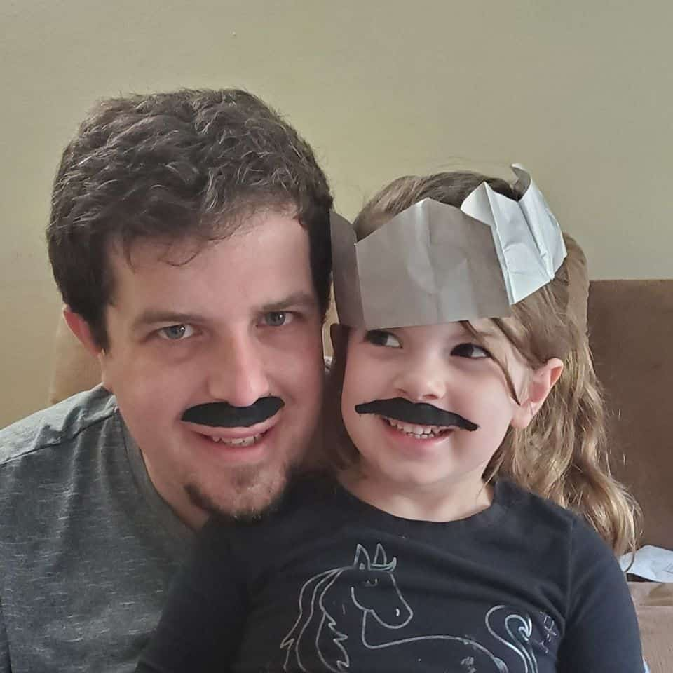 father and daughter wearing fake mustaches