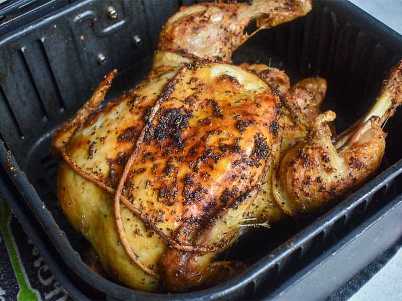roasted whole chicken in a black air fryer basket