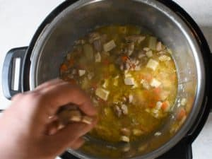a hand is dropping small squares of biscuit dough into a soup of chicken stock, potatoes, chicken and veggies for instant pot chicken and dumplings.