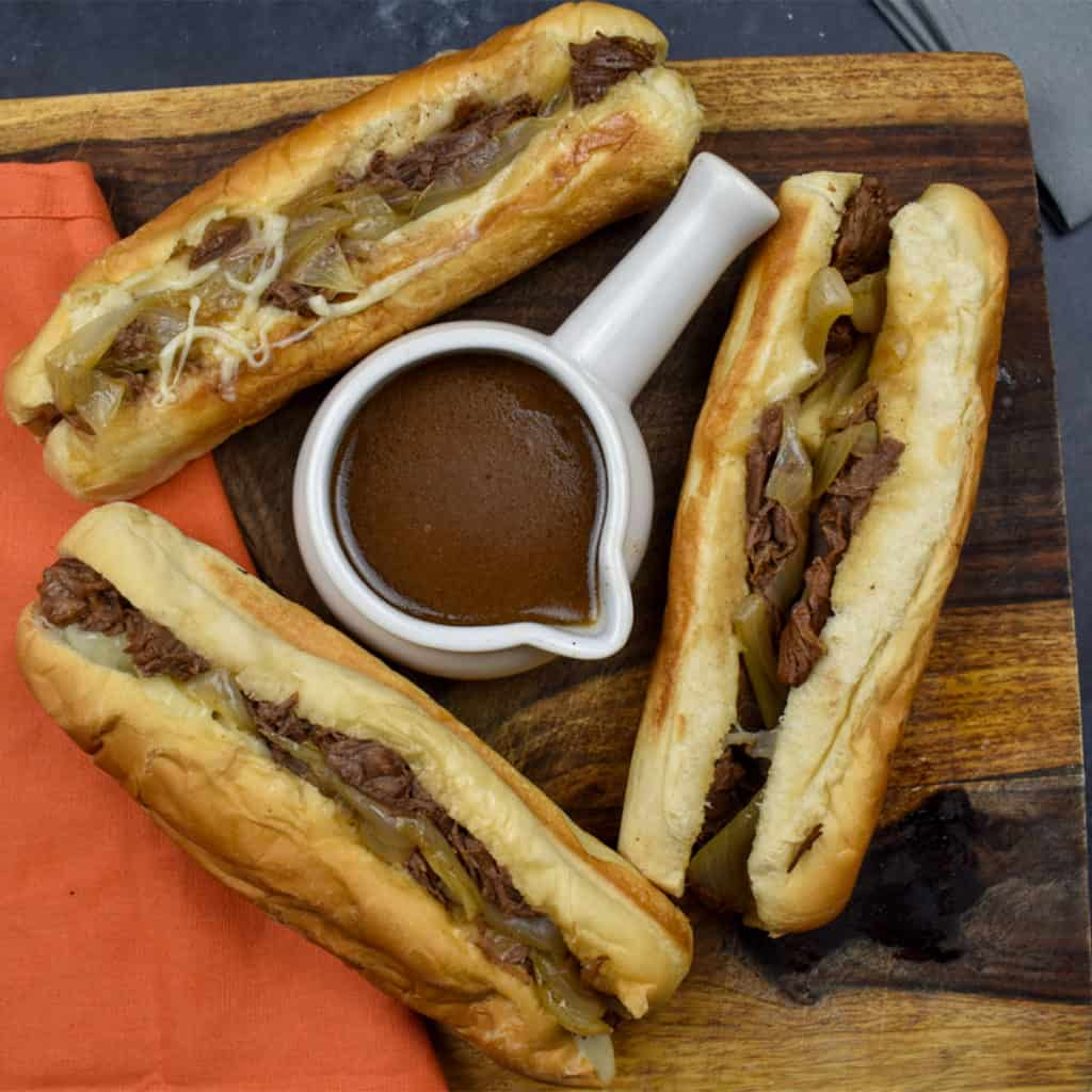 three french dip sandwiches on a wooden board with au jus sauce in a white dipping bowl