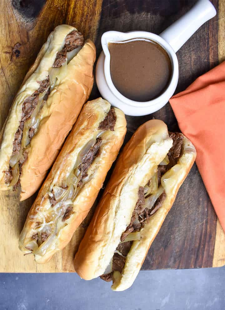 three french dip sandwiches with onions on a wooden cutting board with au jus dipping sauce in a white gravy bowl