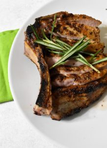 double bone pork chop sliced along the blone, sitting a white plate and topped with rosemary sprigs. There is a green napkin on a white table underneath.