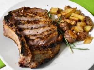 pork chop sliced alongside the bone on a white plate with roasted potatoes alongside.