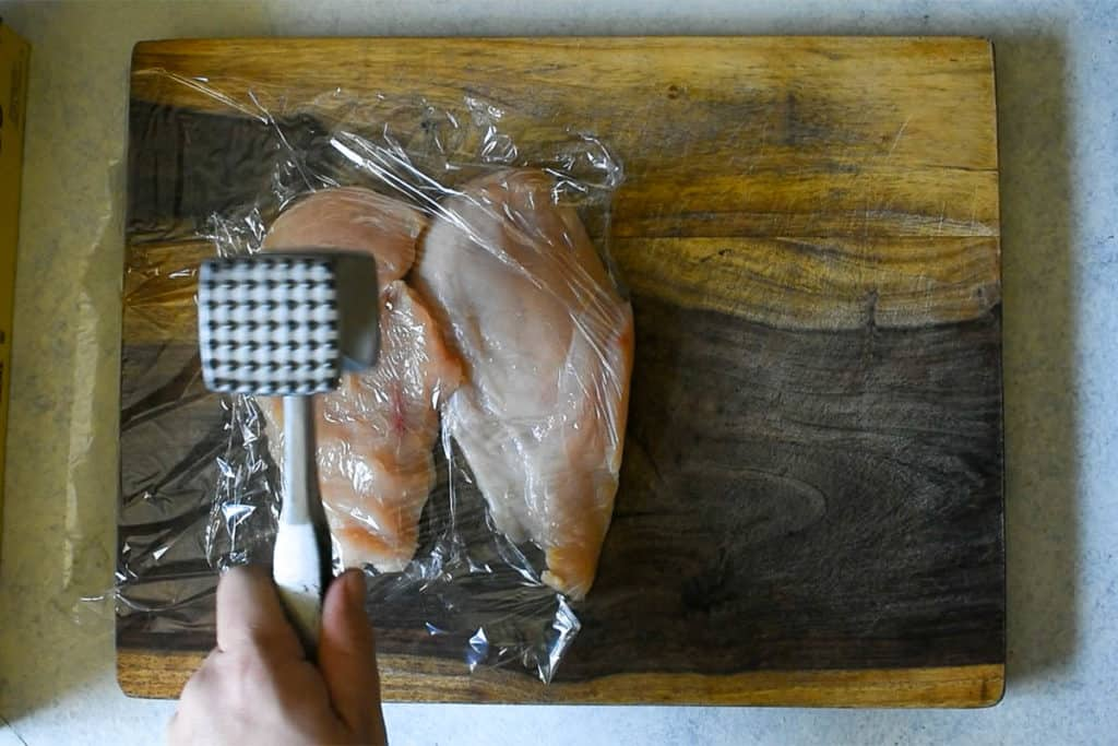 chicken breasts being beaten with a metal meat mallet