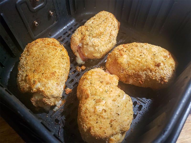 cooked chicken cordon bleu in an air fryer basket