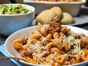 noodles with ground beef and tomato sauce in a whit ebowl with salad and rolls in the background