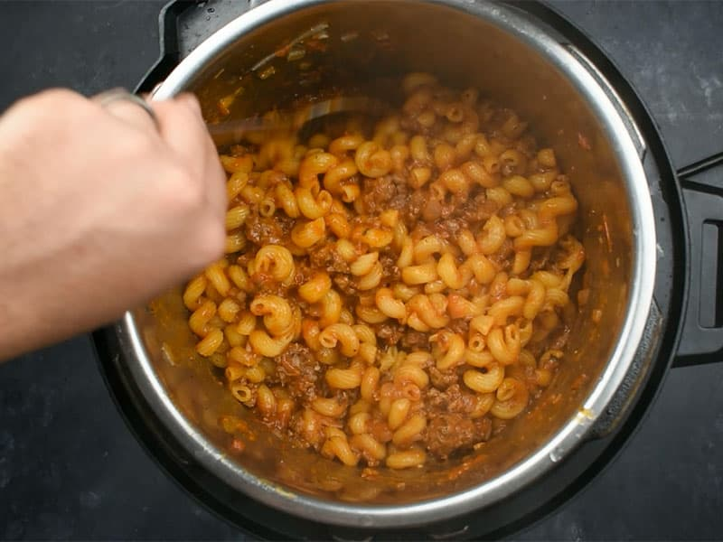 hand stirring cooked goulash in an instant pot